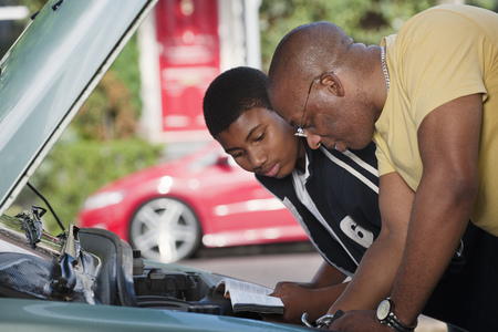taught man: father & son working on car engine LANG_EVOIMAGES