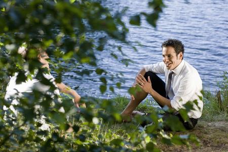 two businessmen talking on lakefront LANG_EVOIMAGES