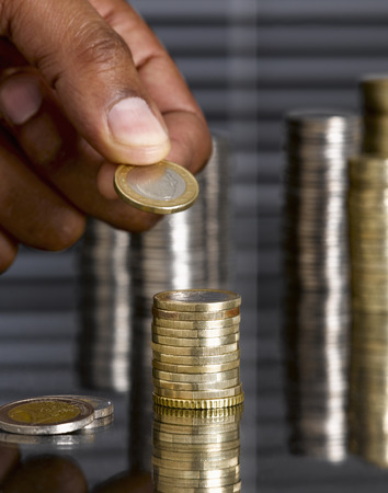 afroamerican: Man stacking euro coins