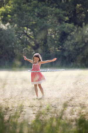 Girl with hula hoop in country field