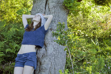 leans on hand: Girl leaning against tree
