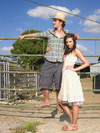 leaning by barrier: couple posing on farm gate