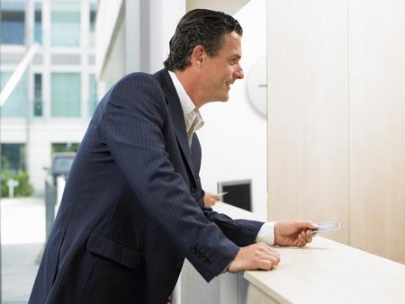 provide: Man with credit card at front desk LANG_EVOIMAGES