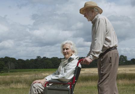 ninety's: Elderly man pushing woman in wheelchair