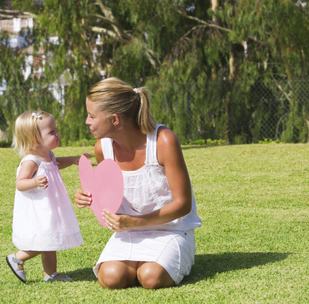 Mother and daughter holding paper heart LANG_EVOIMAGES