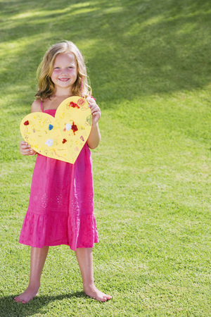 Young girl holding paper heart LANG_EVOIMAGES