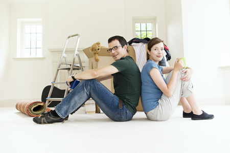 accomplishes: A young couple sitting back to back.
