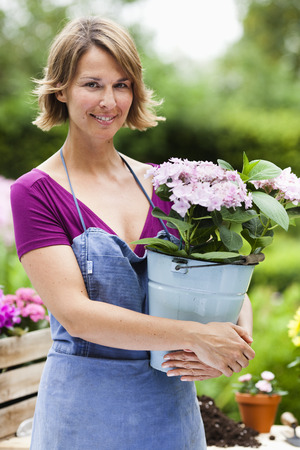 flowered: woman holding a bucket with flowers LANG_EVOIMAGES