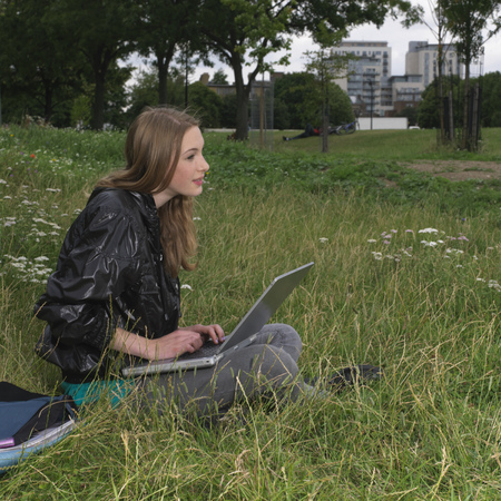 pubescent: Young woman with laptop outside LANG_EVOIMAGES