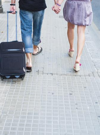 trolly: couple with trolly walking along street