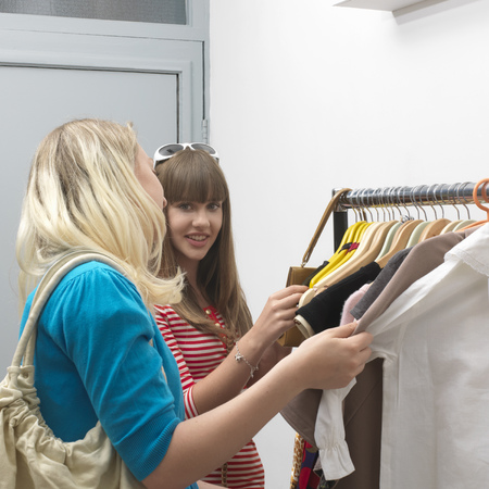 shopping buddies: 2 young women standing at clothes rail LANG_EVOIMAGES