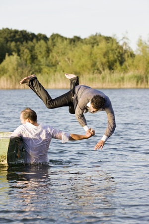 mischeif: businessman throwing friend in water
