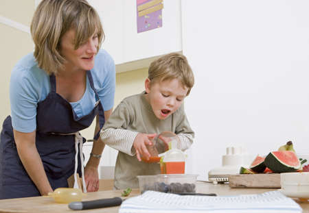 new age: boy and mum making fruit lollies