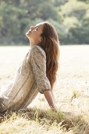 Woman lying back relaxing in field LANG_EVOIMAGES