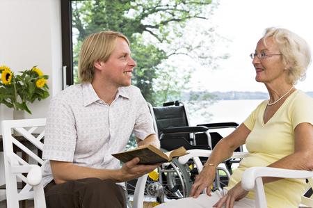 faiths: man reading book to senior woman LANG_EVOIMAGES
