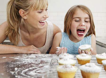 mischeif: Mum and daughter with cakes LANG_EVOIMAGES