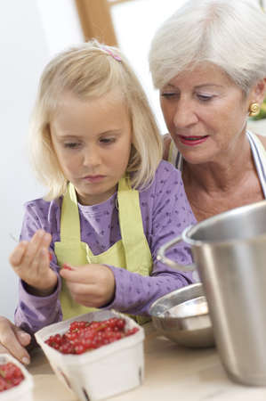 new age: girl with grandmother cooking jam