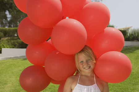 Young girl holding bunch of red balloons LANG_EVOIMAGES