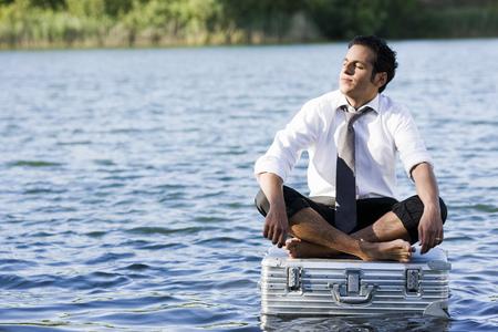 businessman sitting on floating suitcase LANG_EVOIMAGES