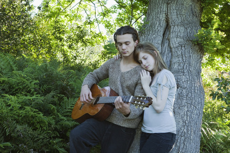 musically: Young man with girl playing guitar LANG_EVOIMAGES