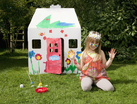 abodes: A girl outside her painted wendy house