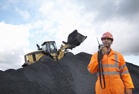 Coal Miner With Digger On Pile Of Coal