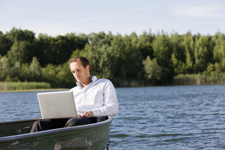 remoteness: businessman with laptop in rowboat