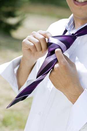 man knotting tie