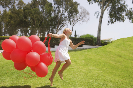 Young girl jumping with red balloons