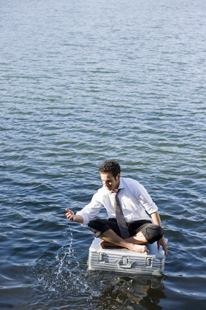 secluded: businessman sitting on floating suitcase LANG_EVOIMAGES