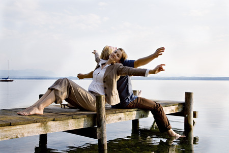 lean back: woman and man sitting on pier at lake