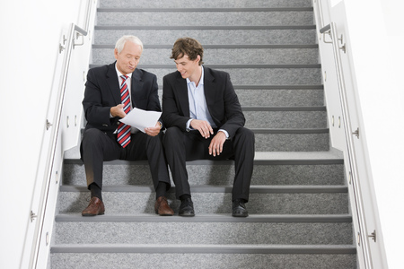motioning: two businessmen on staircase