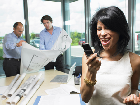 acknowledging: Woman on the phone, men with blue prints