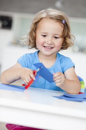 young girl using paper and scissors