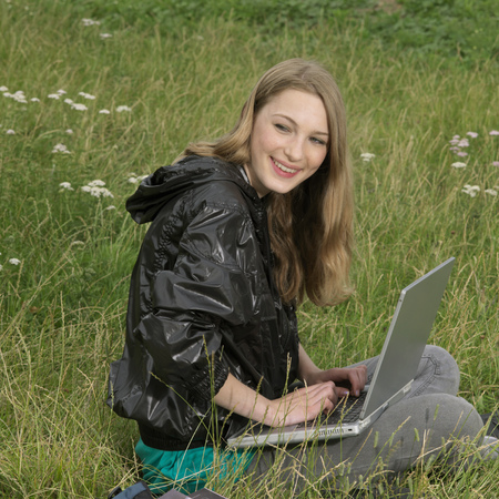 revolved: young woman with laptop in park LANG_EVOIMAGES