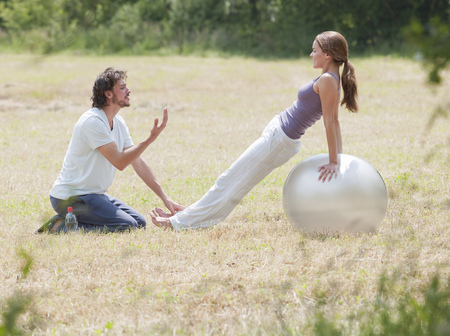 couple on yoga ball stretching