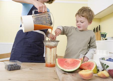 relaciones laborales: Niño y mamá haciendo batidos de frutas