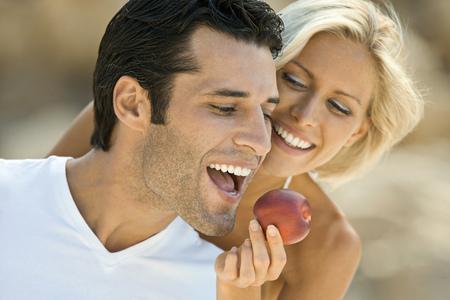 A female feeding a latin man an apple.