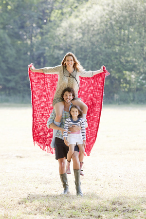 gratified: Family with red blanket in country field
