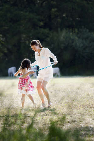 Mother and daughter playing with hoop
