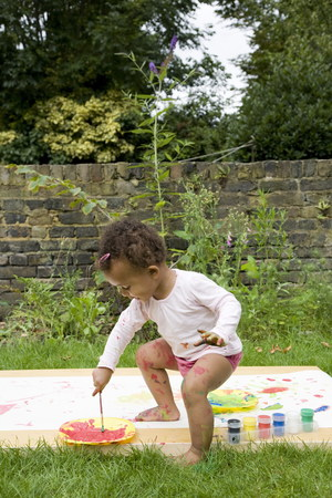 gratified: Child painting in the garden
