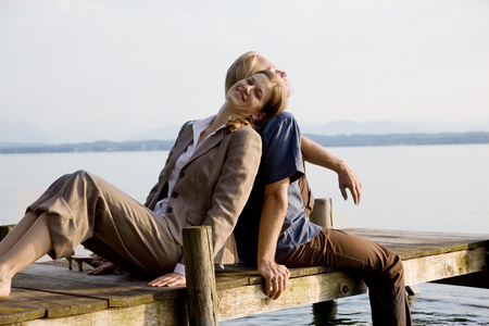 rejoices: woman and man sitting on pier at lake