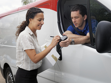 distributing: woman signing for delivery from driver