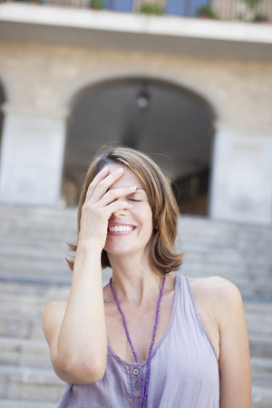 timidity: woman covering her eyes smiling