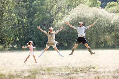 gratified: Family jumping in country field LANG_EVOIMAGES