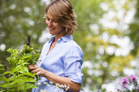 gratified: woman taking care of plants