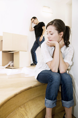 moving box: Young female sitting with head in hands. LANG_EVOIMAGES