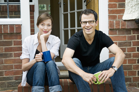 gratified: A young couple sitting on their doorstep