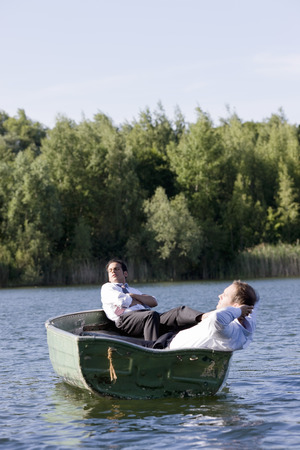 remoteness: two businessmen relaxing in rowboat