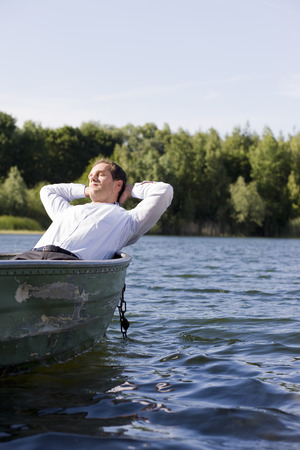 gratified: businessman relaxing in rowboat LANG_EVOIMAGES